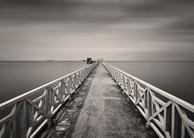 Bridge over sea against cloudy sky