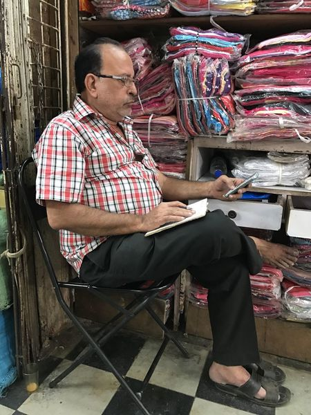 Mobile Conversations Checked Pattern Casual Clothing Real People Full Length Sitting Small Business Plaid Shirt  One Person Eyeglasses  One Man Only Adults Only Working Workshop Day Only Men Indoors  Adult People