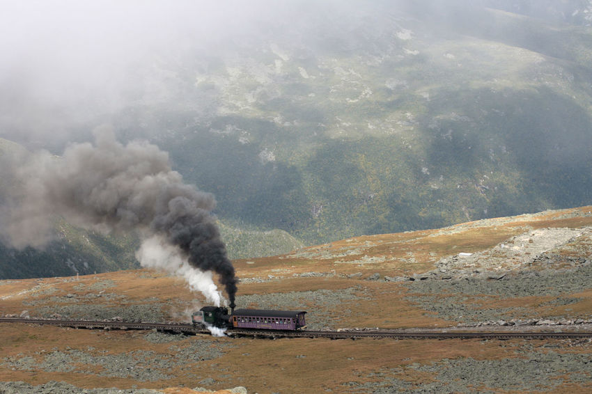 Steam Train of Mount Washington Cog Railway is pusing up Coach to the summit at good weather conditions Blue Sky White Clouds Bretton Woods Mount Washington Cog Railway Narrow Gauge Railway New Hampshire, USA Smoke Air Pollution Beauty In Nature Day Environment Environmental Issues Geology Industry Land Landscape Mode Of Transportation Motion Mountain Nature No People Non-urban Scene Outdoors Pollution Scenics - Nature Smoke - Physical Structure Summit Transportation Water