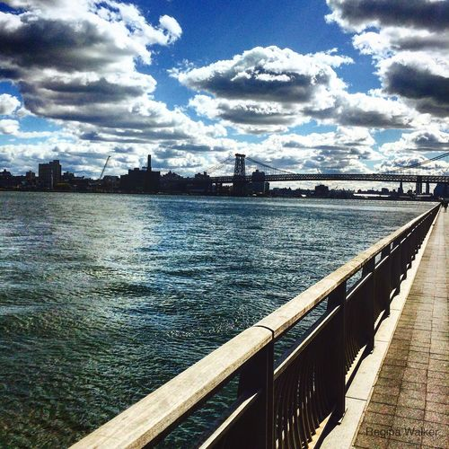 Pier on river against cloudy sky