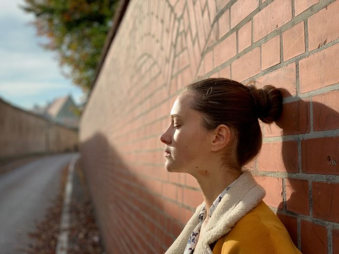 Young woman standing by brick wall