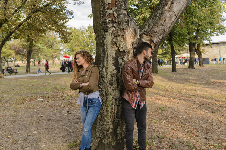 Young couple ignoring each other in the public park Casual Clothing Couple - Relationship Day Group Of People Incidental People Jeans Leisure Activity Men Nature Outdoors People Plant Real People Three Quarter Length Tree Tree Trunk Trunk Women Young Adult Young Men Young Women