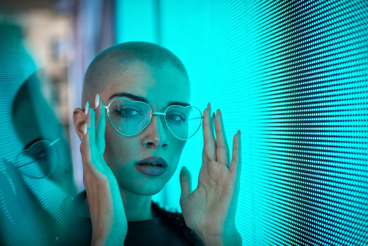 Portrait of young woman with shaved head standing against abstract backgrounds