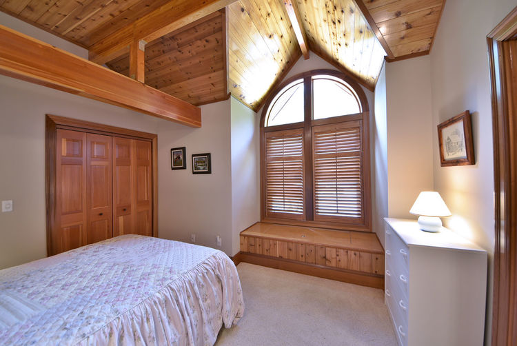 Retire in comfort to the luxurious guest quarters. Architecture Bed Bedroom Cathedral Ceiling Curtain Day Dresser Exposed Wood Beams Guest Quarters Indoors  Log Cabin No People Rustic Charm Sleeping Quarters Window Bench Wood - Material Wood Paneling