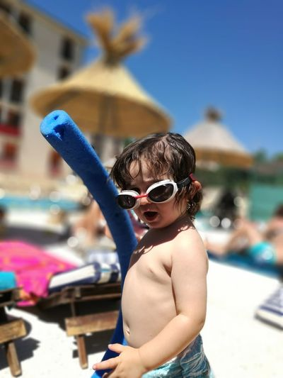 Portrait of baby boy wearing swimming goggles at resort on sunny day
