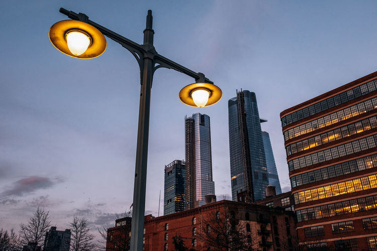 Low angle view of illuminated street light by building against sky