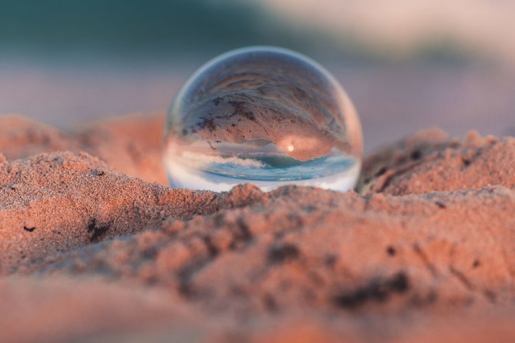 Close-up of crystal ball on sand at beach