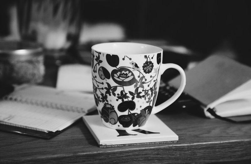 Close-Up Of Mug On Book At Table