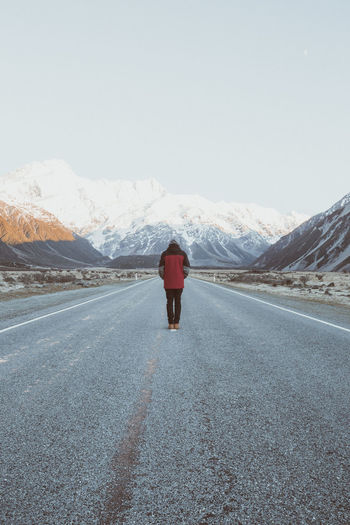 Man standing in road leading up to Mt. Cook. Clear Sky Cold Temperature Day Landscape Mountain Nature No People Outdoors Road Sky Snow Transportation Winter