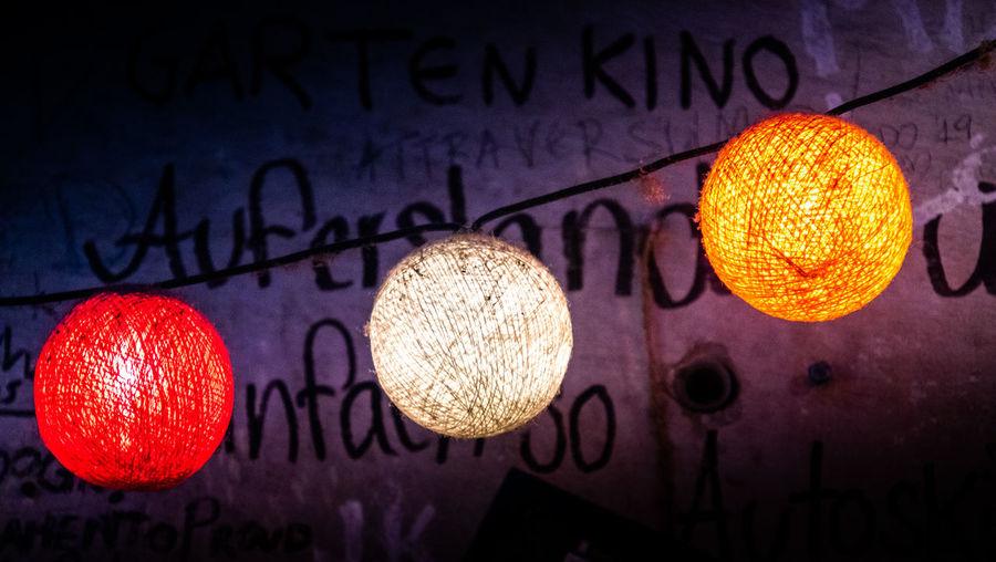 Close-up of illuminated lanterns hanging on wall