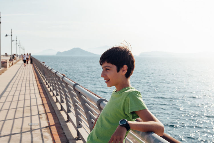Happy boy on a sea promenade, bay of Naples, Italy Bay Of Naples, Italy. Beauty In Nature Boys Casual Clothing Childhood Clear Sky Day Leisure Activity Lifestyles Mountain Naples Napoli Nature One Person Outdoors People Real People Sea Sky Water Young Adult Young Women
