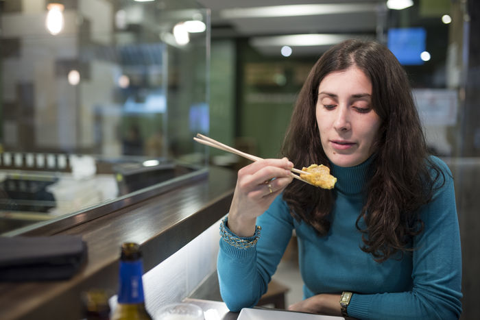 woman eating sushi Bar Casual Clothing Chopsticks Eating Focus On Foreground Food Food And Drink Healthy Eating Holding Indoors  Japanese  Long Hair Night One Person People Raw Food Real People Restaurant Sashimi  Sitting Sushi Tempura Woman Young Adult Young Women