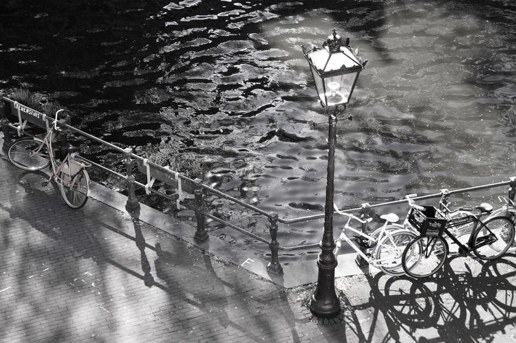 Amsterdam Black And White Bycicle Day Flower Box High Angle View Light And Shadow Monochrome No People Outdoors Railing Street Light Streetphotography Town Canal Tranquility Water Waterreflections  Waves Monochrome Photography
