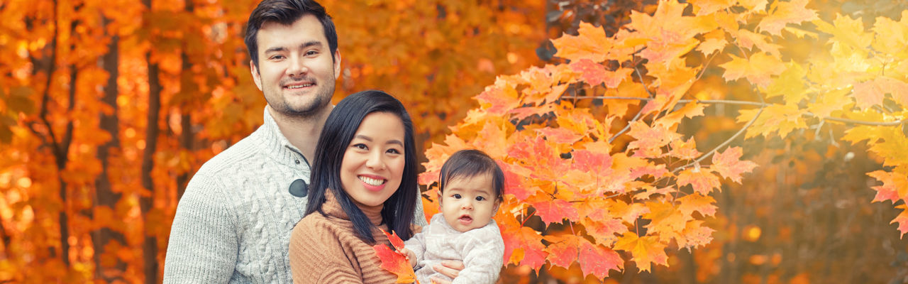 Asian chinese mother and caucasian father dad with baby girl in autumn fall park. family  outdoor
