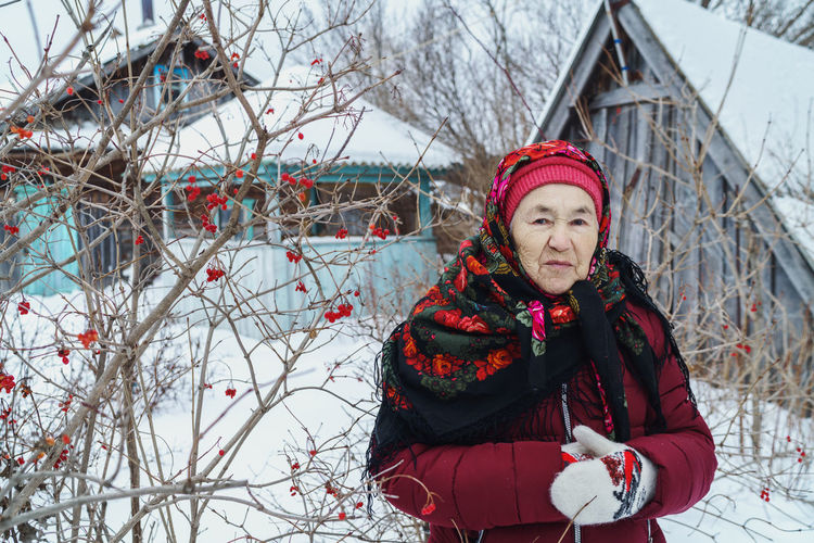 Portrait of woman with red umbrella against trees during winter