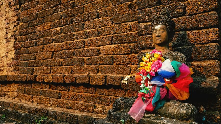 Religious statue by brick wall