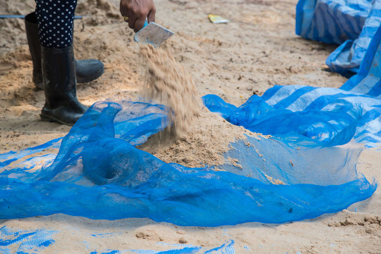 Low section of person cleaning sand at beach