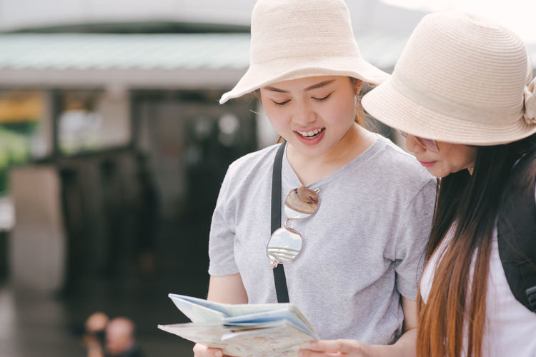 Tourists Reading Map While Standing In City