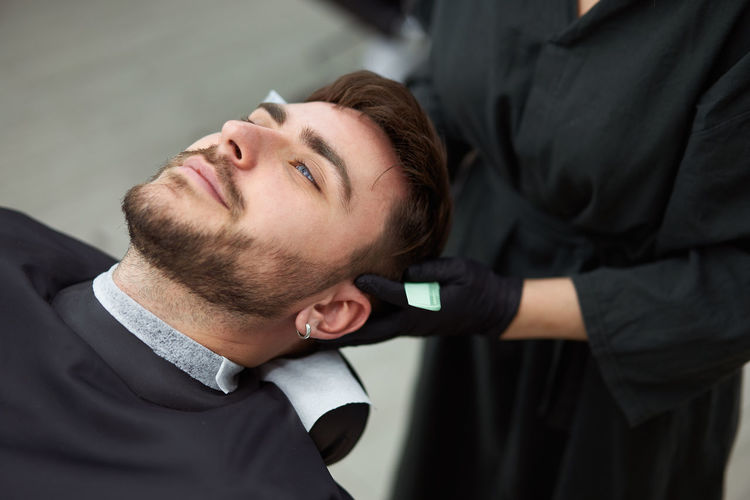 Midsection of female hairdresser cutting man hair in salon