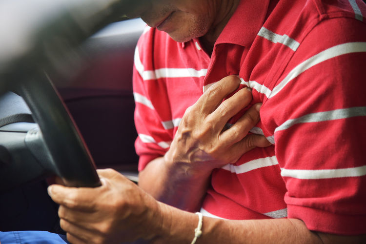 Midsection of man with heart attack while sitting in car