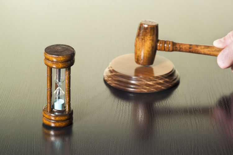 High angle view of gavel with hourglass on wooden table