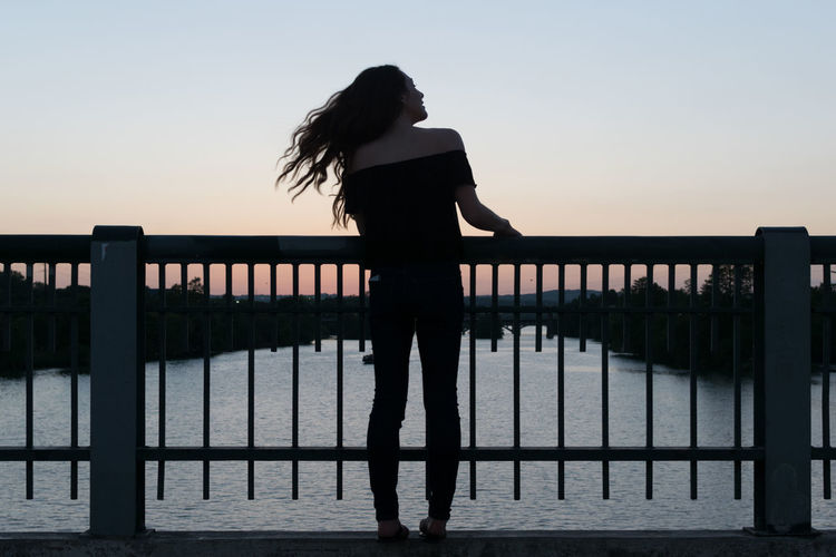 Rear View Of Woman Standing In Front Of River At Sunset