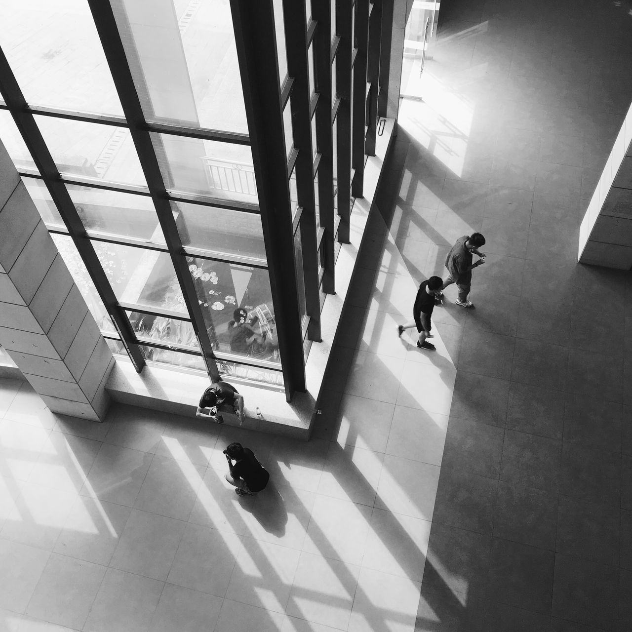 HIGH ANGLE VIEW OF MAN WALKING IN CORRIDOR OF BUILDING