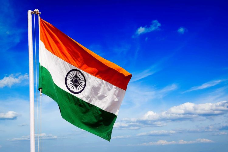 Low angle view of indian flag against blue sky