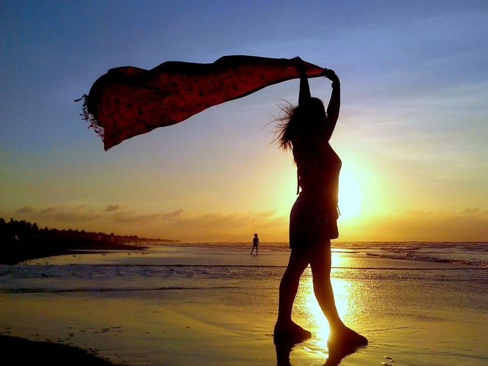 Full length of woman holding scarf while standing at beach during sunset
