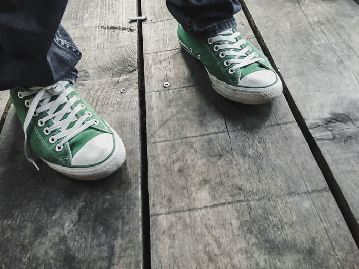 Copy Space Green Color Body Part Canvas Shoe Day Flooring Footpath High Angle View Human Body Part Human Foot Human Leg Human Limb Jeans Leisure Activity Lifestyles Low Section Men One Person Outdoors Plank Real People Shoe Standing Unrecognizable Person Wood - Material