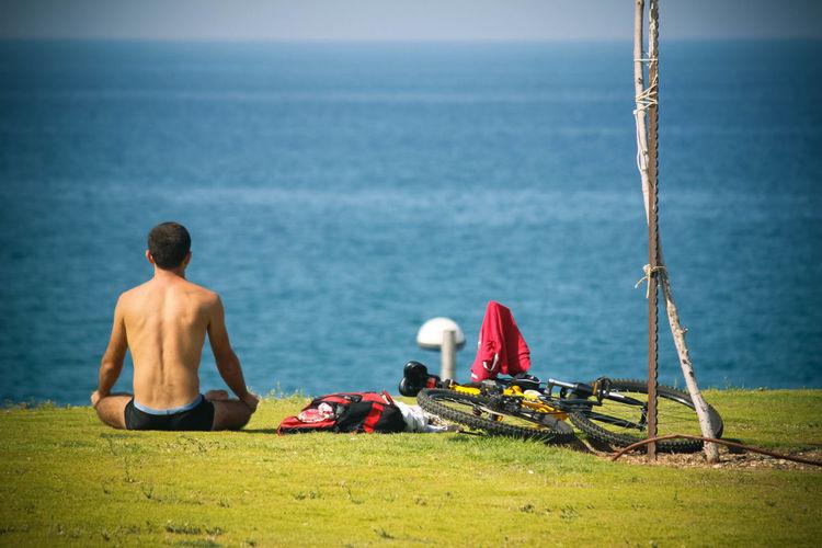 Shirtless Man Overlooking Calm Sea