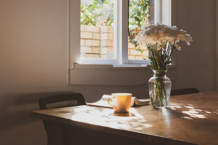 Flowers, tea and book with mottled light Table Indoors  Vase Window Flowering Plant Home Interior Flower No People Nature Cup Day Plant Drink Mug Still Life Food And Drink Domestic Room Sunlight Transparent Glass