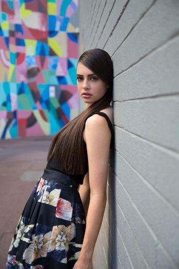 Portrait of teenage girl wearing dress leaning on wall