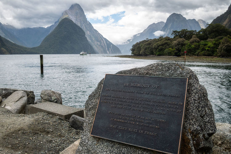 Fjord with impressive mountains in backdrop and monument in foreground. milford sound, new zealand