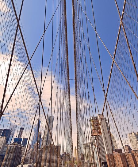 Low Angle View Of Building Against Sky Seen Through Cables Of Brooklyn Bridge
