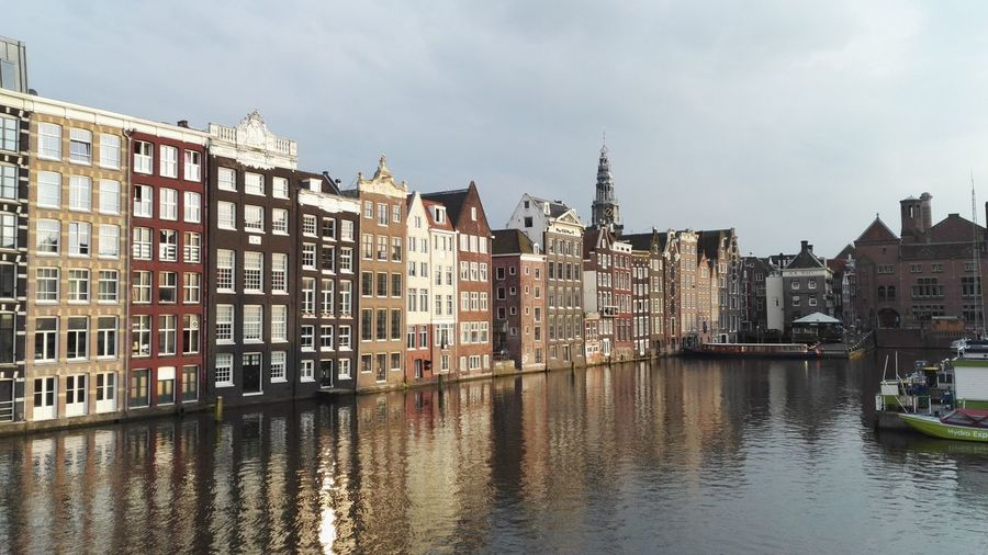 Canal in city against sky