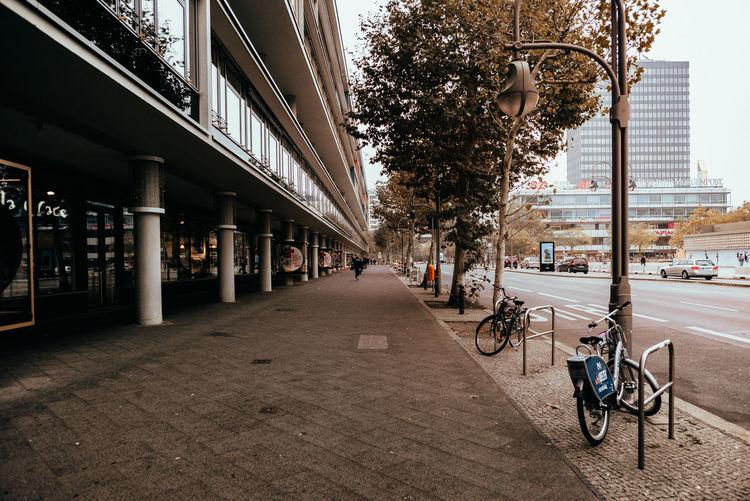 Bicycle on sidewalk by buildings in city