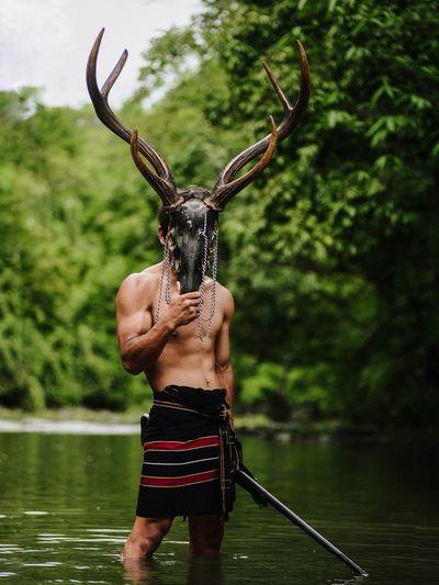 Full length of shirtless man standing in lake
