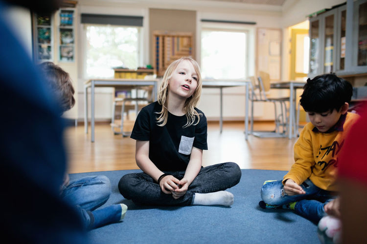 Girl talking while sitting with friends on floor in classroom