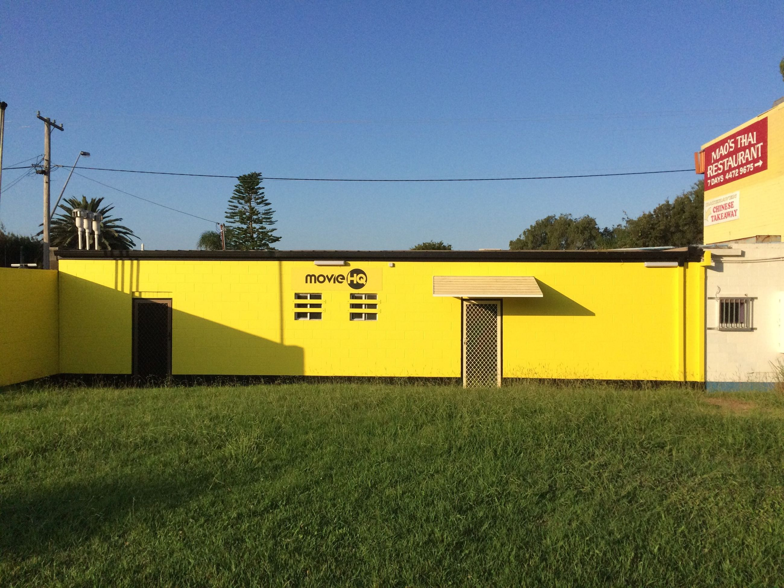 yellow, clear sky, communication, text, western script, built structure, grass, building exterior, architecture, copy space, information sign, field, sign, blue, road sign, guidance, outdoors, day, power line, no people