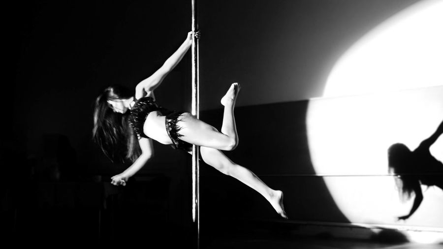 Woman Doing Pole Dance In Darkroom