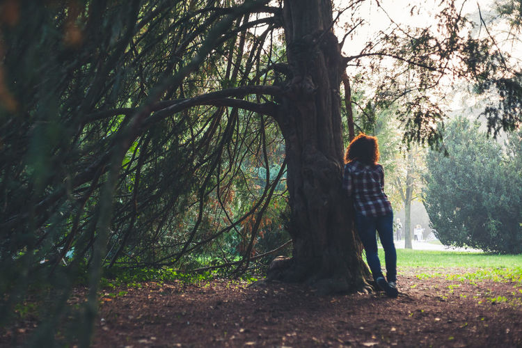 Rear view of woman standing by tree at park