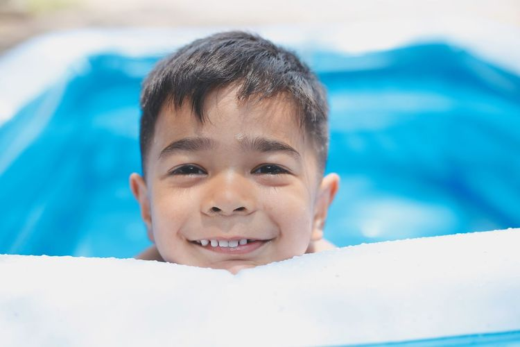 Close-up portrait of smiling boy swimming in pool