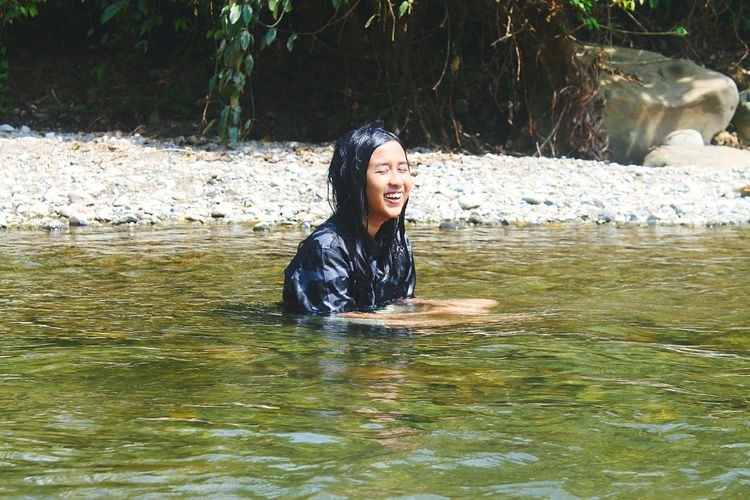 Smiling young woman swimming in lake