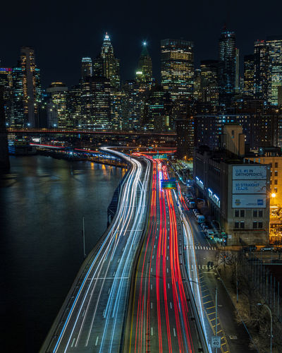 High angle view of light trails on road against buildings in city at night