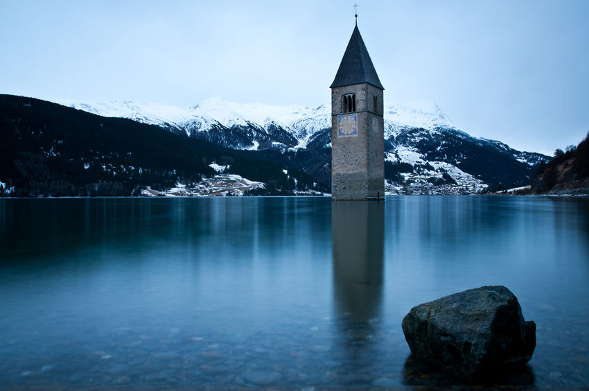 A beautiful view on the tower of the sunken church in the Lake Resia in Tyrol, Italy Architecture Beauty In Nature Blue Cold Temperature Lago Di Resia (Reschensee) Landscape Mountain Mountain Peak Mountain Range No People Outdoors Reflection Reschensee Scenics Snow Tourism Tower Tranquil Scene Tranquility Travel Travel Destinations Vinschgau Water Winter
