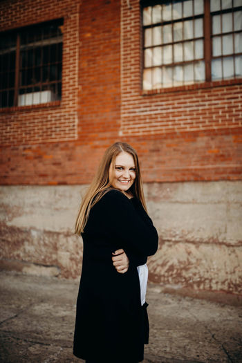Portrait of smiling young woman standing against brick wall