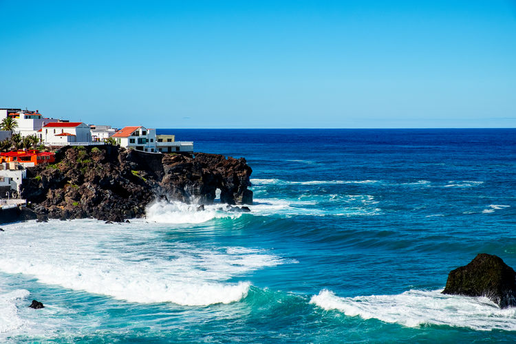 Scenic View Of Waves Splashing Sea Against Clear Blue Sky