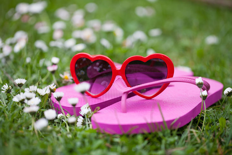 Close-up of heart shape sunglasses on grass