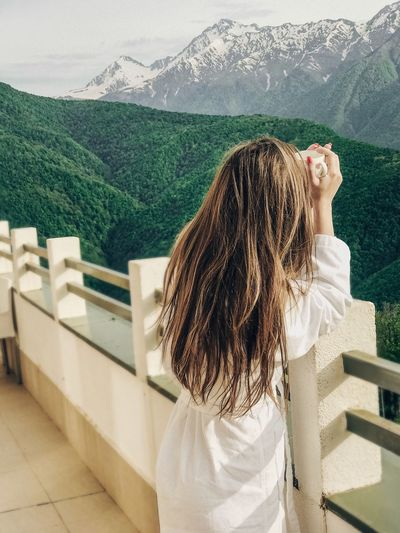 Real People One Person Lifestyles Leisure Activity Women Hair Nature Looking At View Sunlight Long Hair Waist Up Railing Casual Clothing Adult Day Architecture Hairstyle Outdoors Rear View Standing